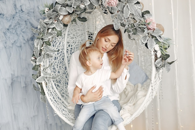 Mulher sentada em um balanço com um bebê. mãe em uma camisa branca está brincando com sua filha. família está se divertindo juntos.