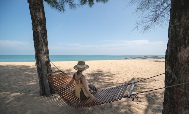 Mulher sentada em um balanço ou berço na praia.