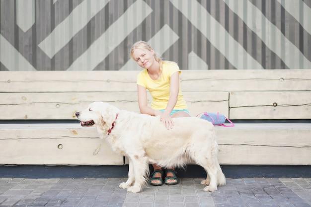 Mulher sentada em um banco acariciando um cachorro