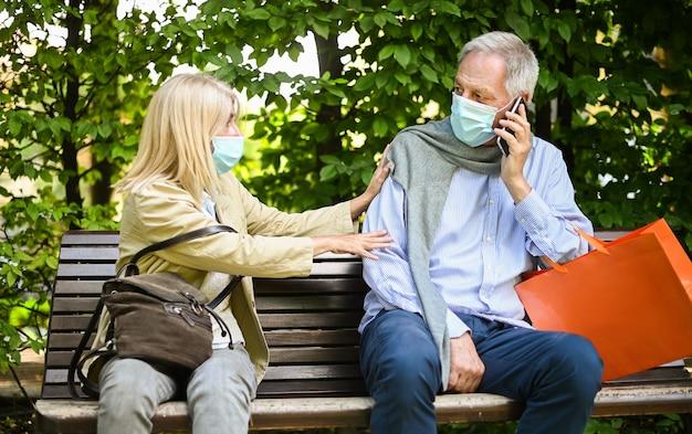 Mulher sentada em um banco com raiva porque um homem não se importa com o distanciamento social durante os tempos de coronavírus
