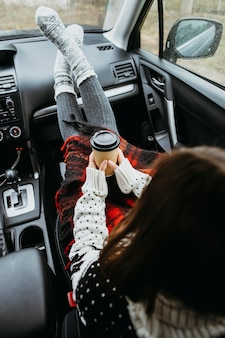 Mulher sentada em um carro com uma xícara de café na parte traseira