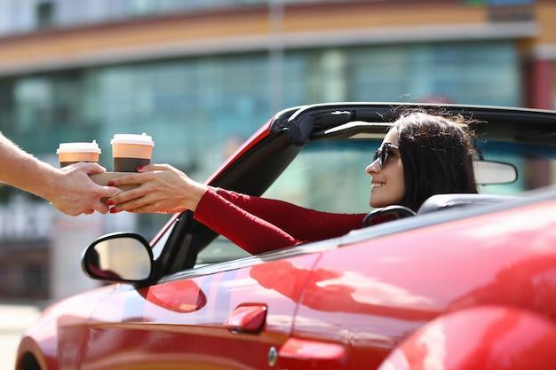 Mulher sentada em um carro conversível é servida em xícaras de café