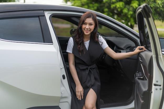 Mulher sentada em um carro e abra a porta