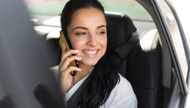 Mulher sentada em um carro e falando ao telefone