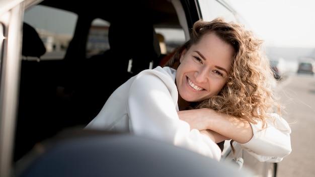 Mulher sentada em um carro e sorri