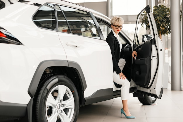 Mulher sentada em um carro na concessionária.