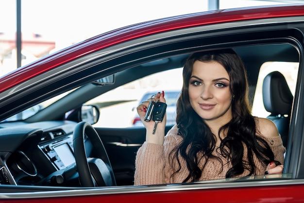 Mulher sentada em um carro novo no showroom