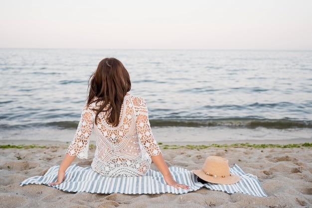 Mulher sentada em um cobertor de costas