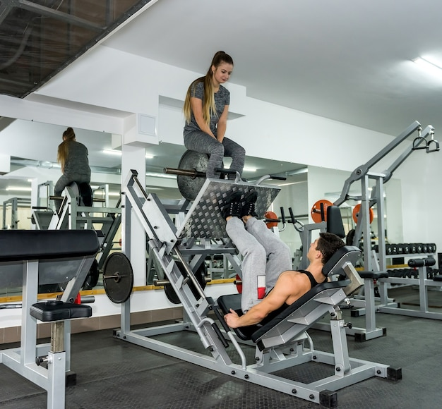 Mulher sentada em um equipamento esportivo como peso para homem