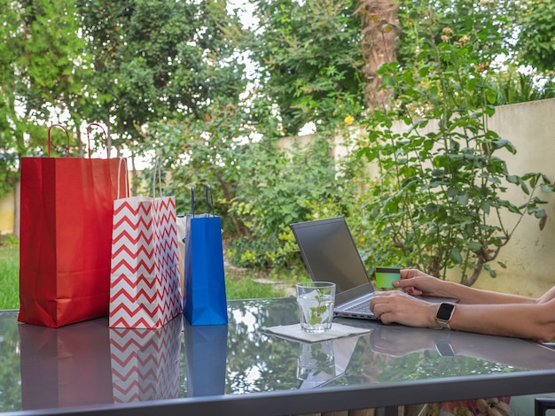 Mulher sentada em um jardim fazendo compras em um computador laptop. conceito de compras online.
