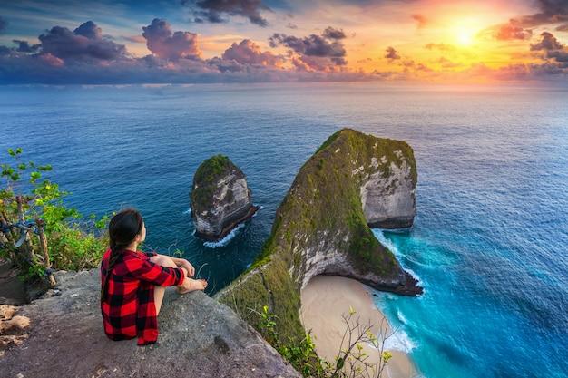 Mulher sentada em um penhasco olhando o pôr do sol na praia de kelingking, na ilha de nusa penida, em bali, na indonésia