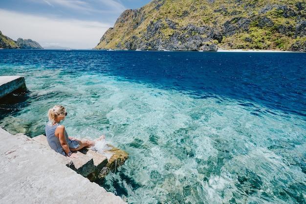 Mulher sentada em um píer curtindo a lagoa azul do oceano em el nido, palawan, filipinas