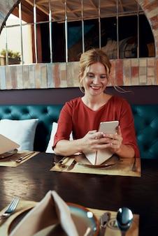 Mulher sentada em um restaurante e mandando mensagens de texto