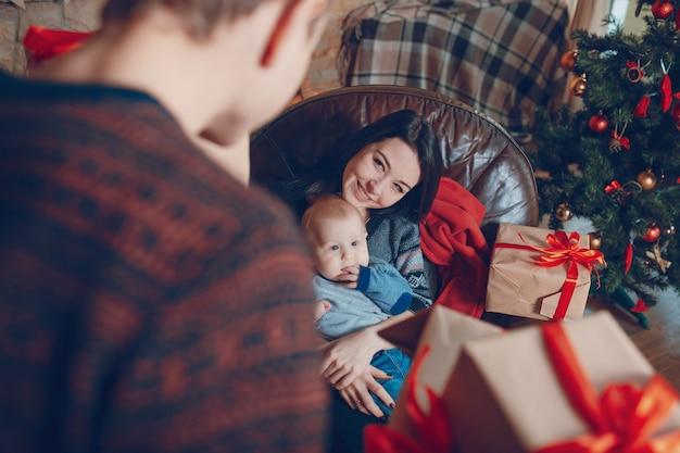 Mulher sentada em um sofá com um bebê nos braços e com uma montanha de presentes marrons com curva vermelha