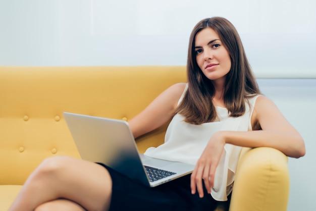 Mulher sentada em um sofá com um laptop sobre as pernas