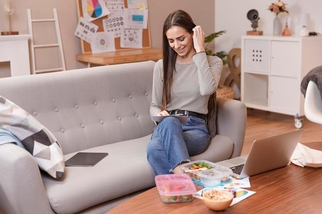 Mulher sentada em um sofá e trabalha