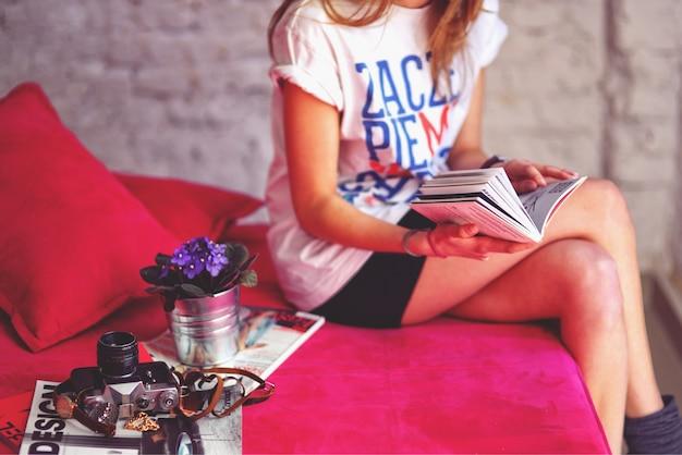 Mulher sentada em um sofá lendo uma revista