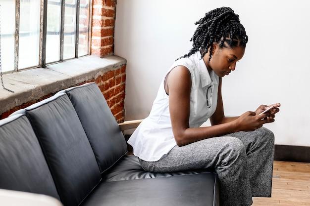 Mulher sentada em um sofá usando smartphone