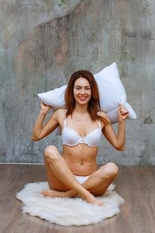 Mulher sentada em um tapete fofo no chão, segurando um travesseiro na cabeça e posando de sutiã e calça branca.