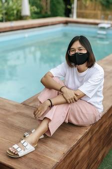 Mulher sentada em um terraço de madeira à beira da piscina.