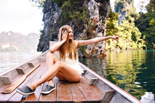 Mulher sentada em um velho barco tradicional da tailândia explorando o parque nacional khao sok