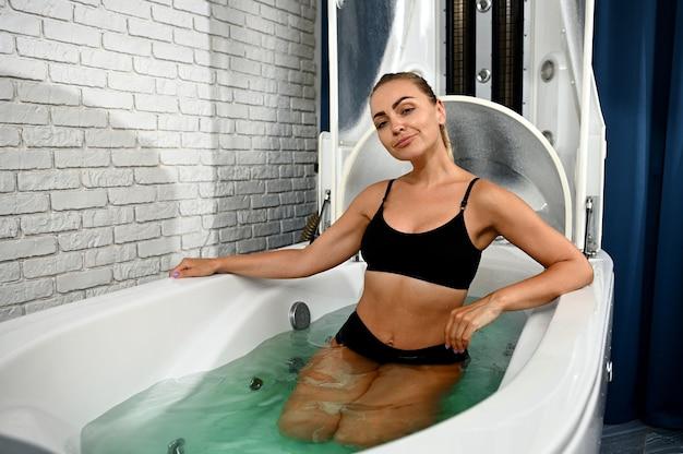 Mulher sentada em uma banheira recebendo vibromassagem e hidromassagem em cápsula de spa para perda de peso, terapia anticelulite, anti-envelhecimento e antiestresse