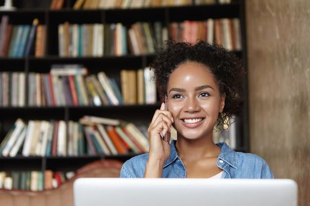Mulher sentada em uma biblioteca com seu laptop