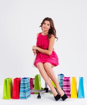 Mulher sentada em uma cadeira ao lado de sacolas de compras