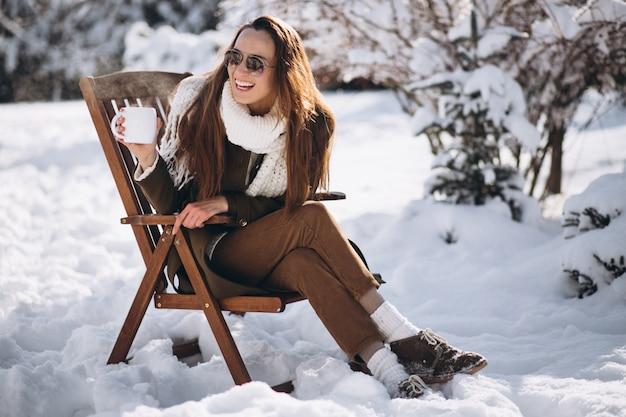 Mulher sentada em uma cadeira com café fora no inverno