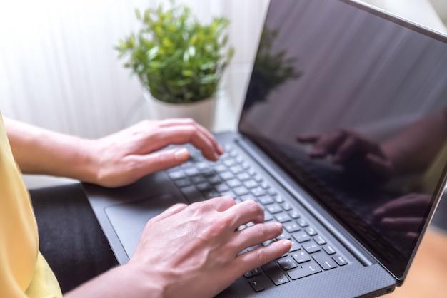 Mulher sentada em uma cadeira com um laptop no colo