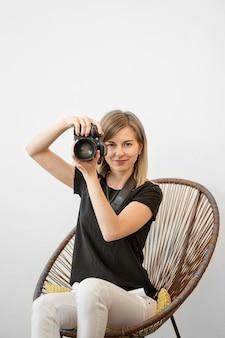 Mulher sentada em uma cadeira e se preparando para tirar uma foto