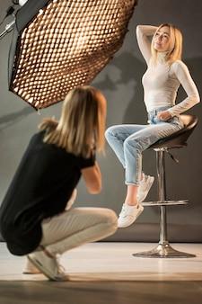 Mulher sentada em uma cadeira e sendo fotografada