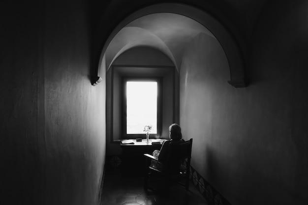 Mulher sentada em uma cadeira em silhueta em uma caverna antiga