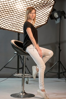 Mulher sentada em uma cadeira lateralmente