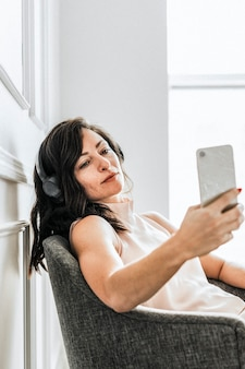 Mulher sentada em uma cadeira ouvindo música