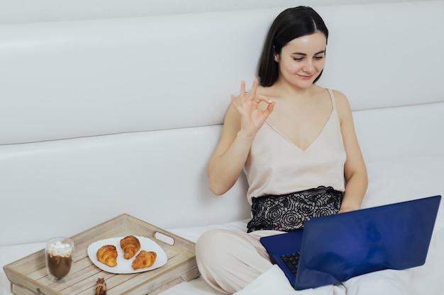 Mulher sentada em uma cama de manhã usando laptop