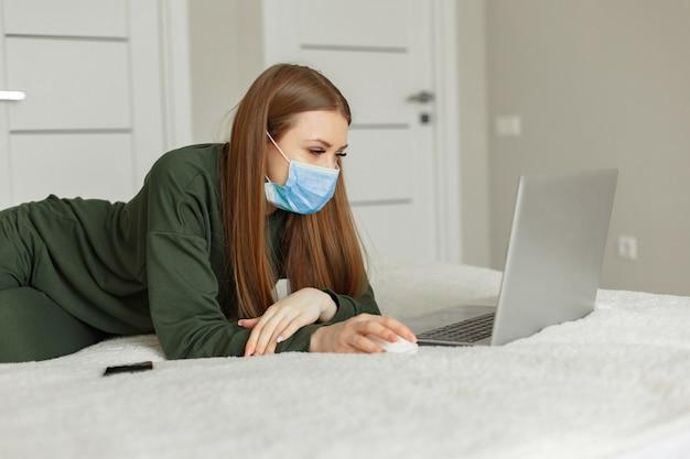 Mulher sentada em uma cama e usa um laptop