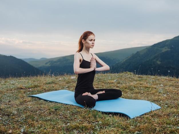Mulher sentada em uma esteira de meditação ioga asana natureza ar fresco.