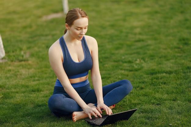 Mulher sentada em uma grama e usa um laptop