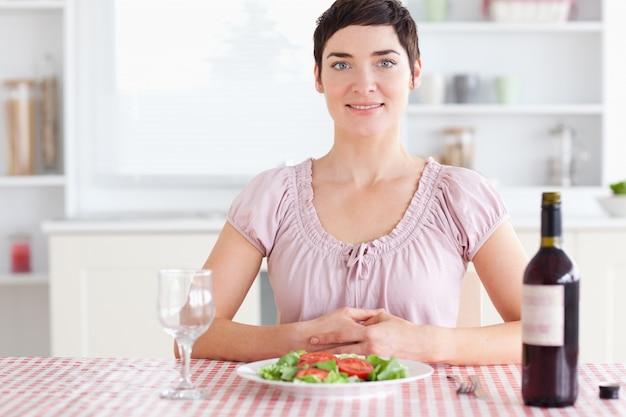 Mulher sentada em uma mesa com vinho para almoço
