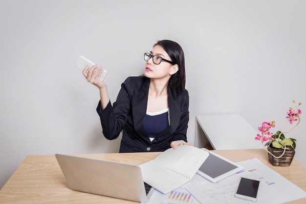 Mulher sentada em uma mesa usando um controle remoto
