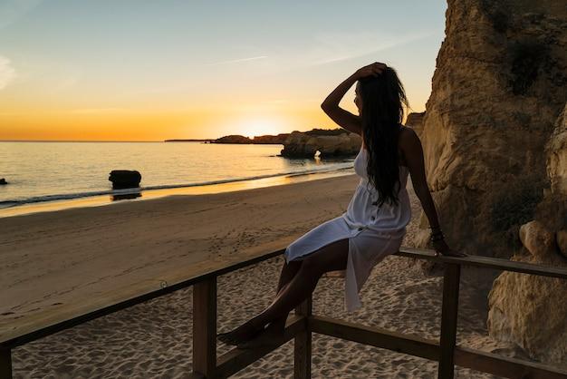 Mulher sentada em uma passarela olhando o pôr do sol na praia do algarve, portugal Foto Premium
