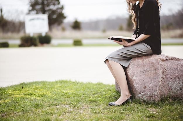 Mulher sentada em uma pedra enquanto lê um livro