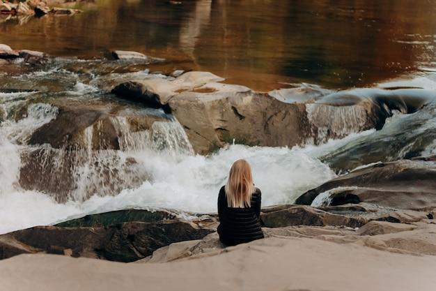 Mulher sentada em uma pedra perto de um rio selvagem nas montanhas