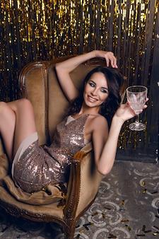 Mulher sentada em uma poltrona e segurando uma taça de vinho