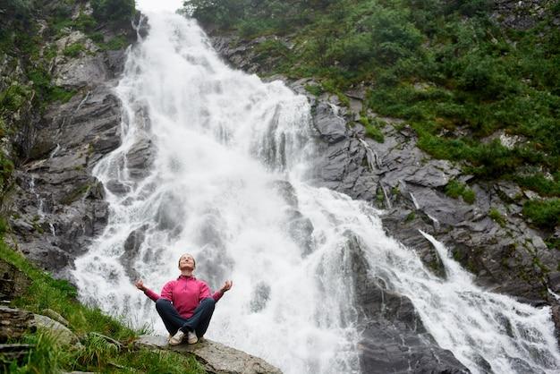 Mulher sentada em uma pose de ioga na grande cachoeira poderosa