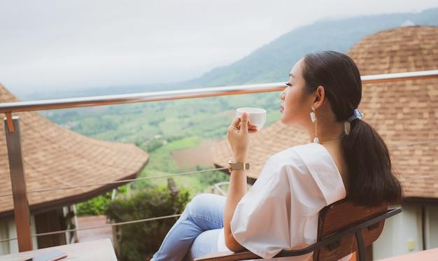 Mulher sentada em uma terrca, apreciando a paisagem asiática