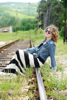 Mulher sentada em vias férreas