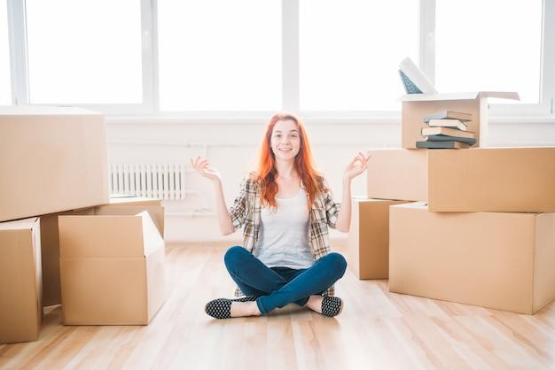 Mulher sentada entre caixas de papelão, inauguração de casa