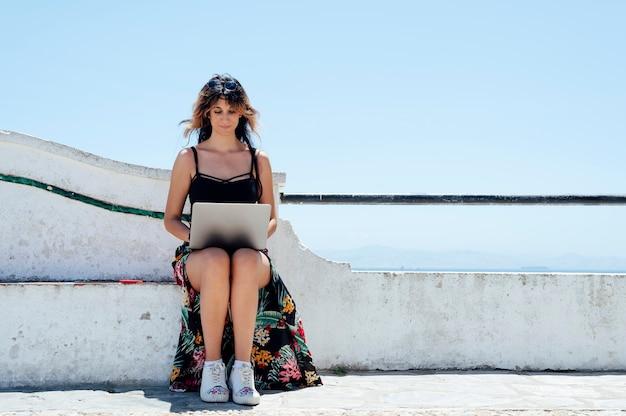 Mulher sentada escrevendo com laptop perto do mar
